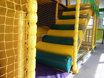 worn green and yellow entrance logs on soft play area