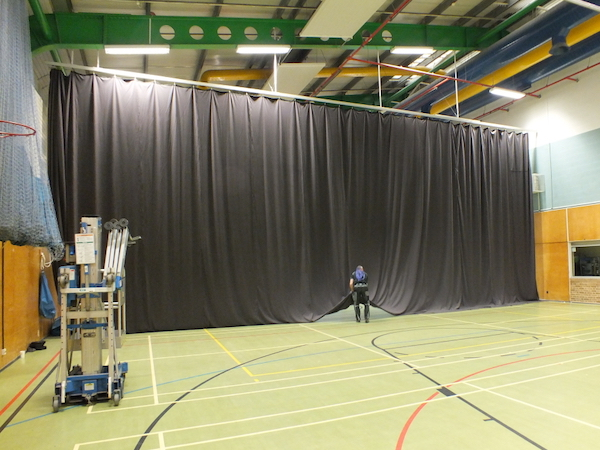 Repaired black sports arena curtain fitted